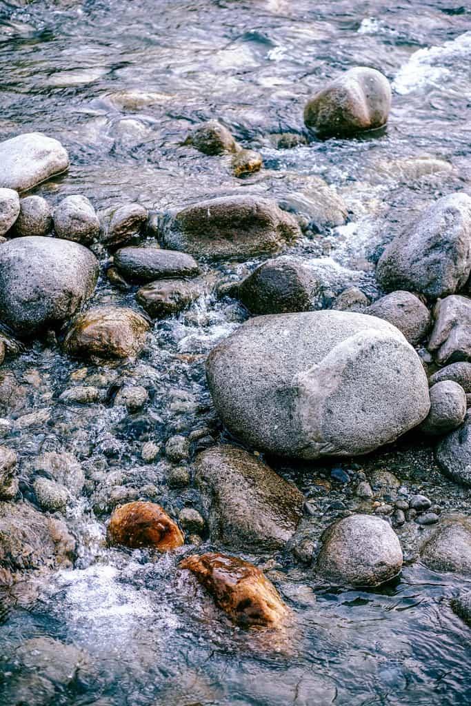 Close up shot of water flowing through round smooth rocks in Manali, India.