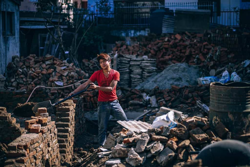 Young Nepali man working with a shovel at a construction site.