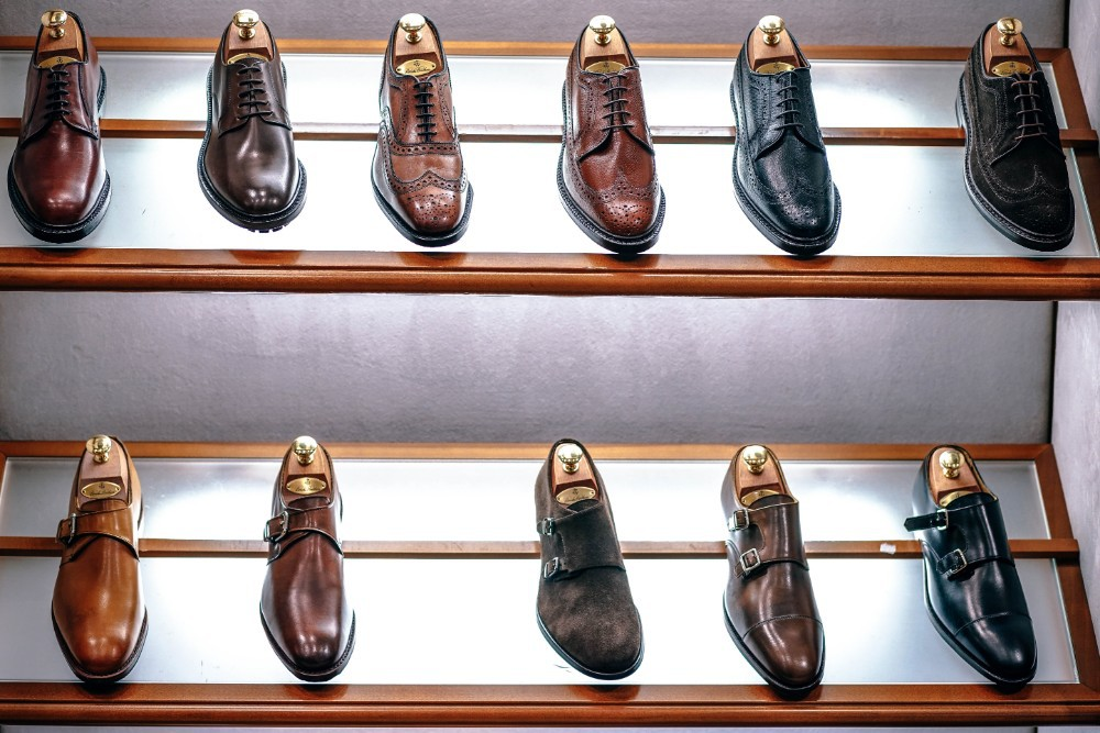 Bunch of classy mens shoes on display inside a retail store.