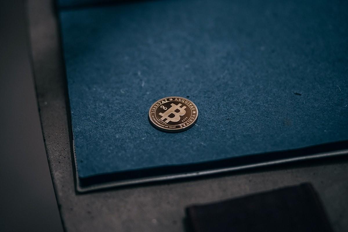 Gold-Bitcoin-Coin-against-a-Blue-Draft-Board-min