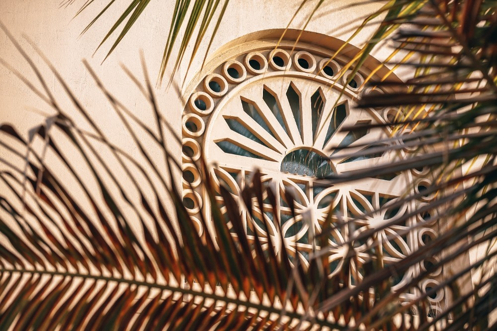 Beautifully Designed Islamic Window Photographed Behind Palm Tree Leaves