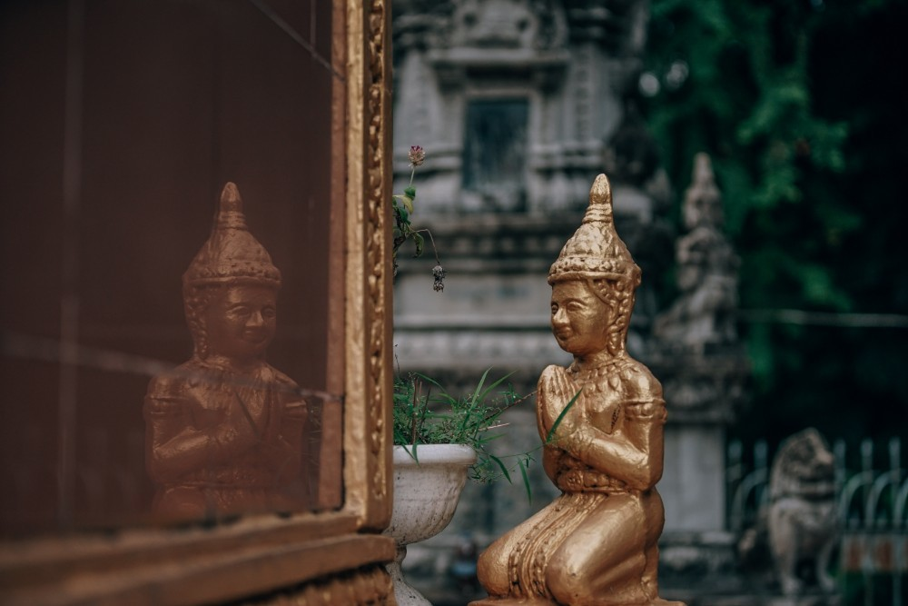 Golden-Buddhist-Statue-Praying-outside-of-a-Temple