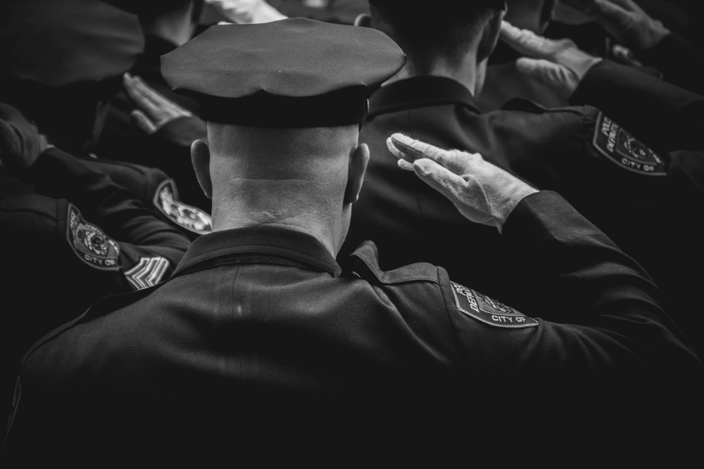 Police officer in a hat and uniform among other police officers giving honor