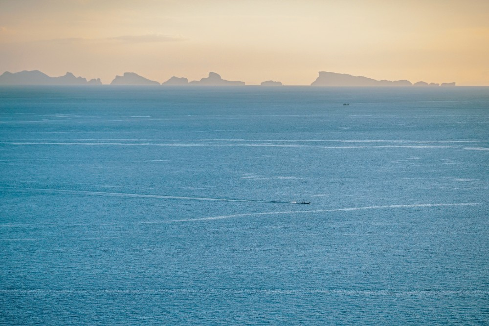 Small-Boat-Floating-in-the-Blue-Sea-at-Sunset