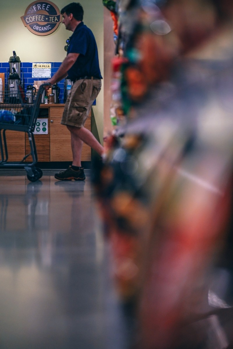 Man Pushing a Grocery Cart Photographed Behind a Full Shelf