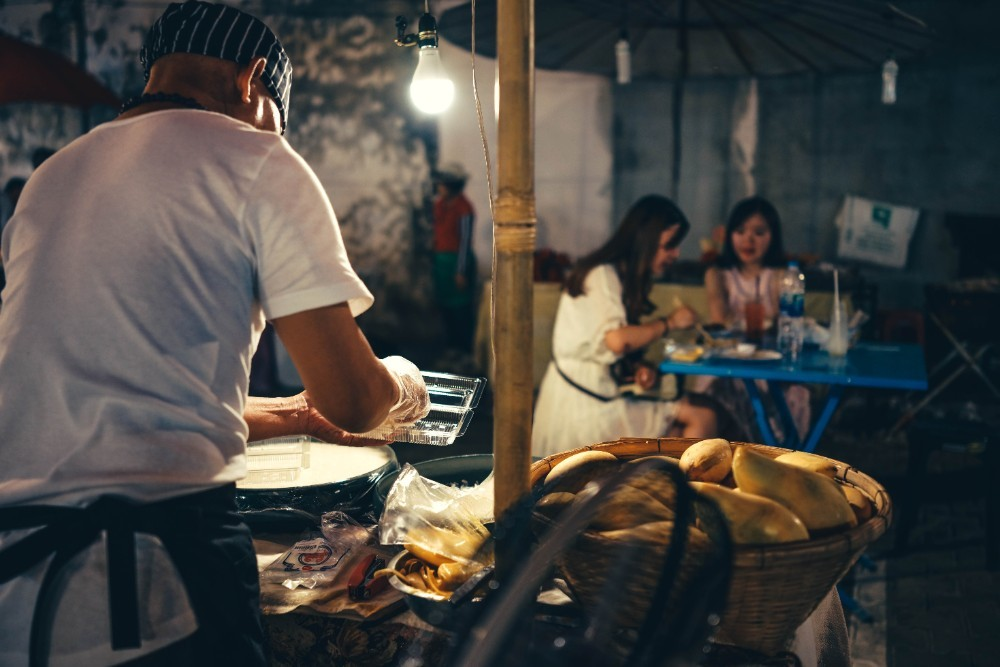 Man working behind a fruit stand at the night market photographed from behind.