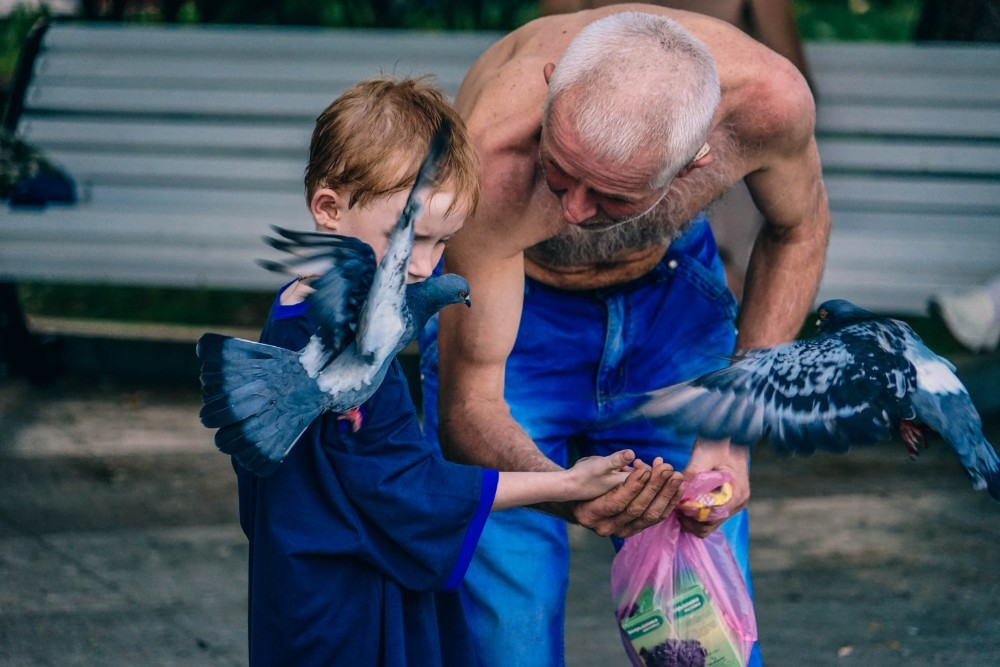 Man Teaching a Young Kid how to Feed Birds