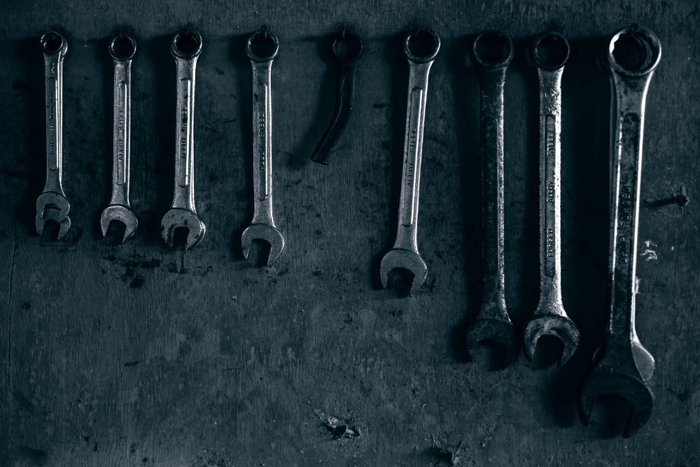 Metal Wrenches Hanging on the Wall in Low Light