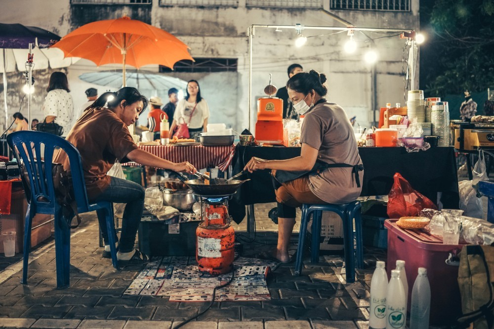 Two Thai Women Frying Food over a Gas Tank at a Night Market
