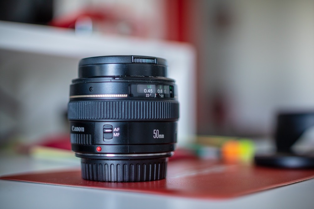 selective focus photography of black Canon camera lens