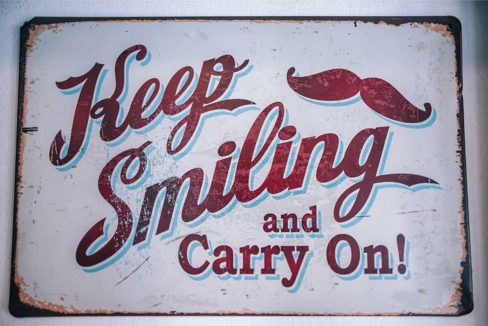 "Café-Sign-Saying-""Keep-Smiling-and-Carry-On"""