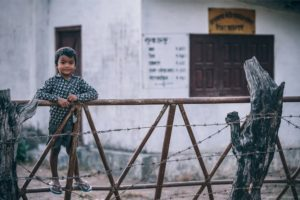 Cute Nepali Boy Standing at a Fence and Looking at the Camera