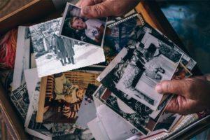Hands Going Through Old Family Photos