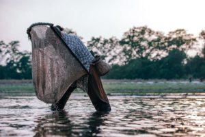 Nepali Woman Holding a Round Fishing Net to Catch Small Fish at Sunset