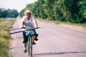Old Woman Smiling at the Camera while Riding a Bicycle