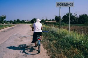Older Woman Driving a Bicycle in a Country Side