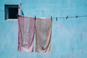 Towels Drying on a Cloth Drying Wire with a Big Light Blue Wall in the Background