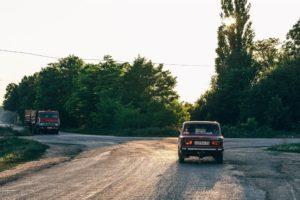 Vintage Car Driving at Sunset