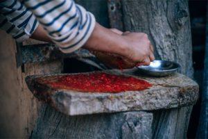 Woman Making Chutney on a Stone Board