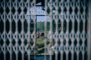 Woman Walking a Cow Photographed Through a Metal Fence