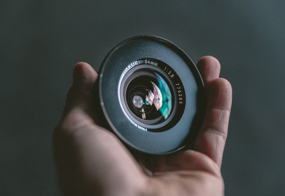 person-holding-black-camera-lens
