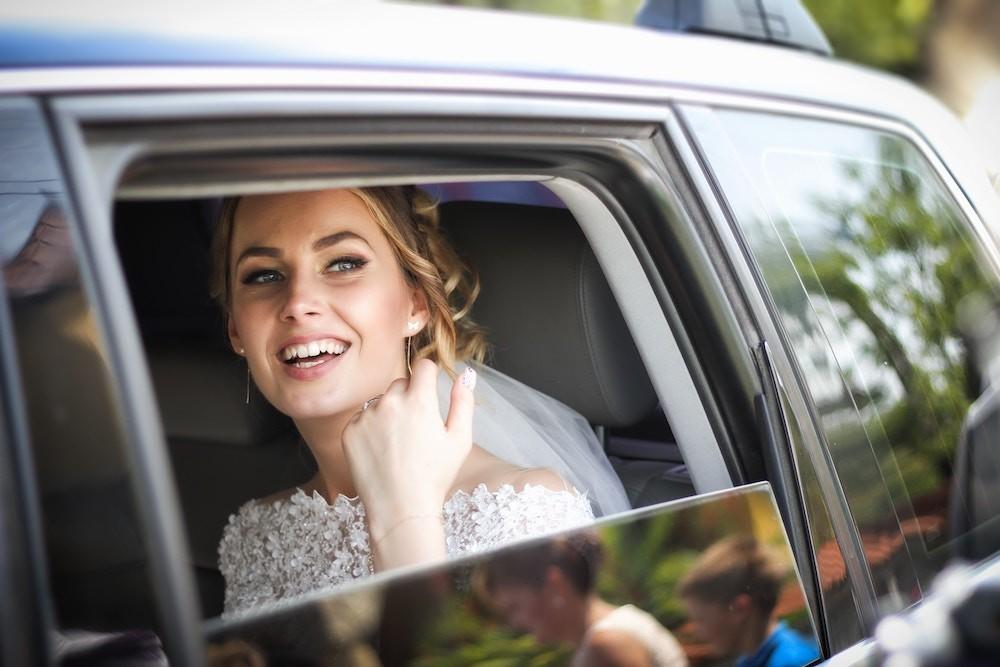 woman wearing wedding dress smiling inside car