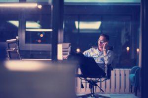 businessman using mobile phone in dark office PHZ