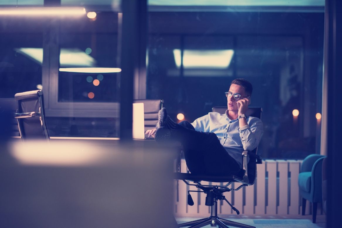 businessman using mobile phone in dark office PHZ