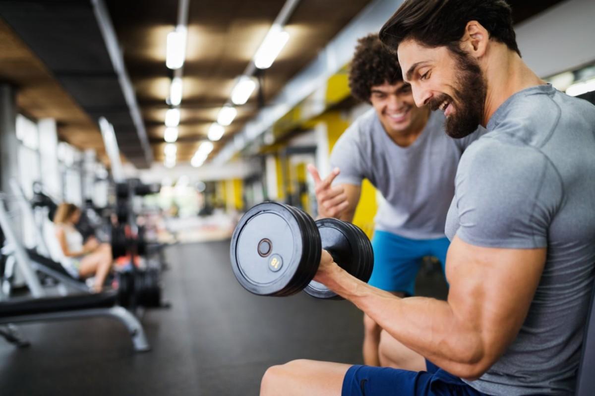 muscular bodybuilder guy doing exercises in gym ASEKGH