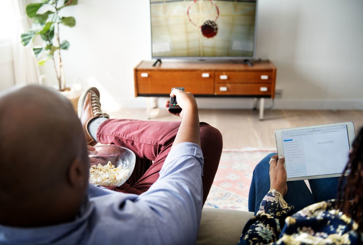 couple-watching-tv-at-home-together-PC4X6MD