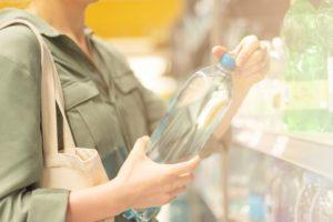 girl choosing bottle of drinking water in grocery QXSDYN