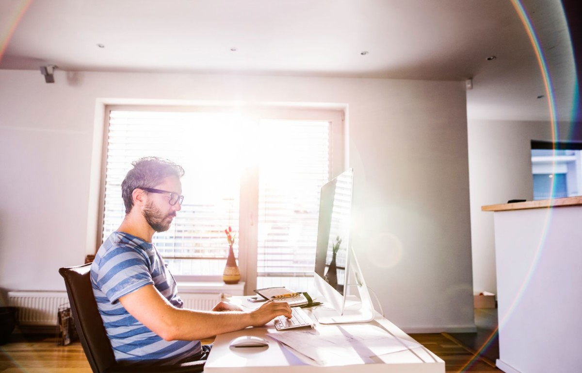 man sitting at desk working from home on computer PYAXPY