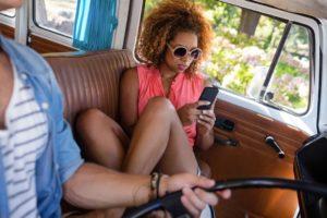 woman using mobile phone while travelling ACZHSJ