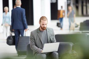 typing on laptop in airport NRWZBX