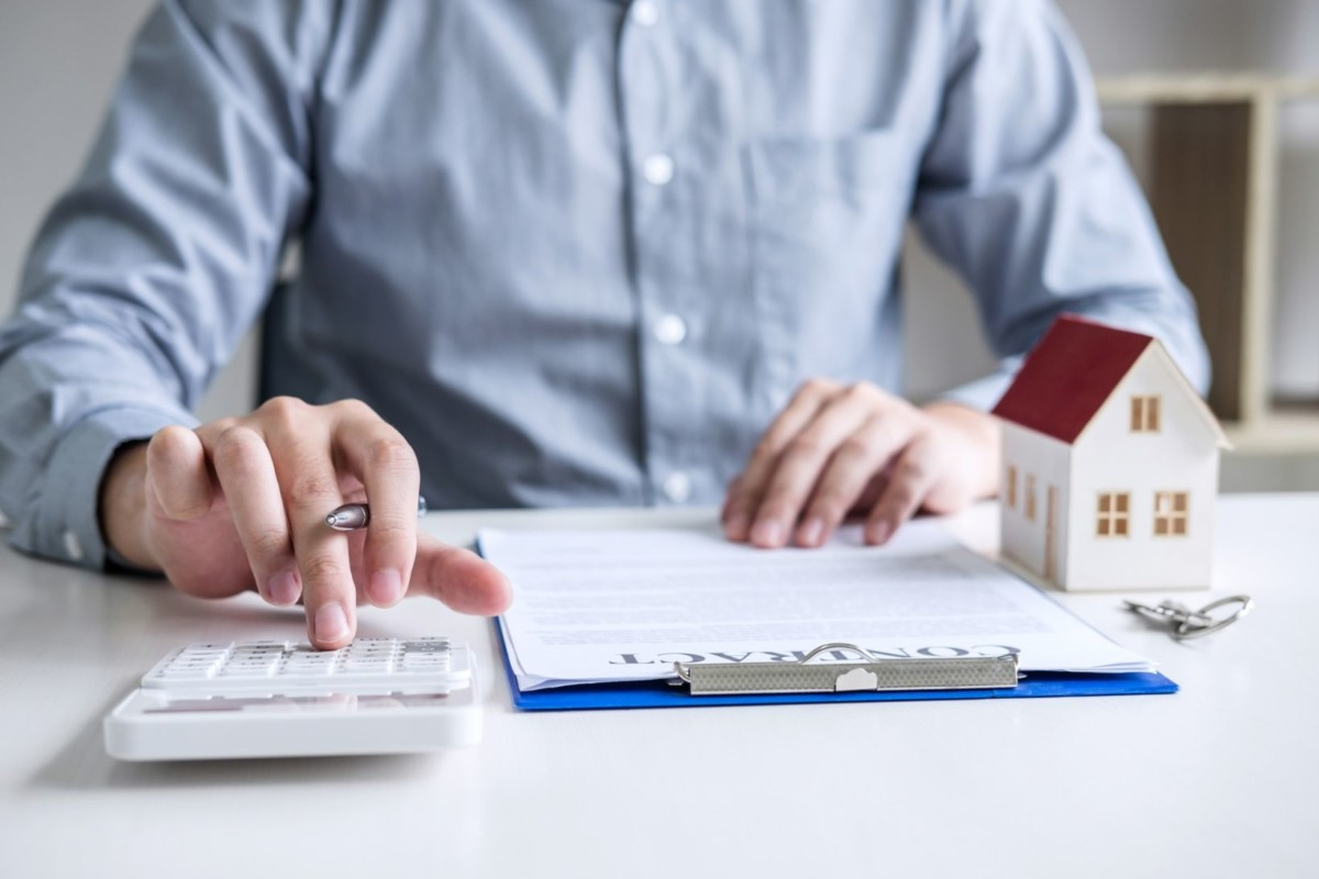 businessman working doing finances and calculation cost of real estate investment while be signing to t lRKjvm