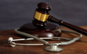 judge gavel and a stethoscope on a wooden desk PVVCT