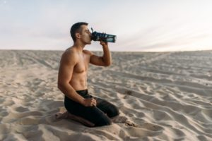 male athlete drinks water after workout in desert SP