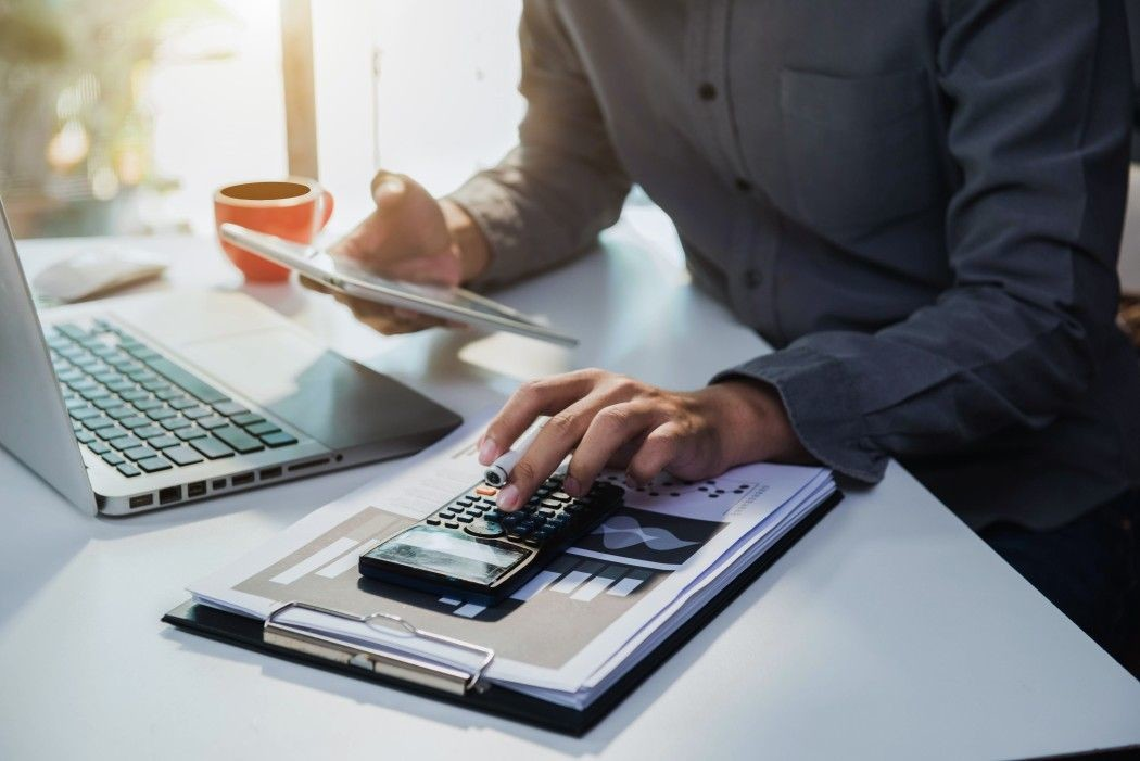 male businessman working on desk office with using a calculator and tablet to calculate the numbers t bxNKm