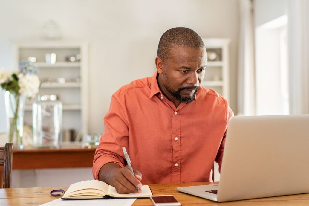 mature man working on laptop at home ZNBKW