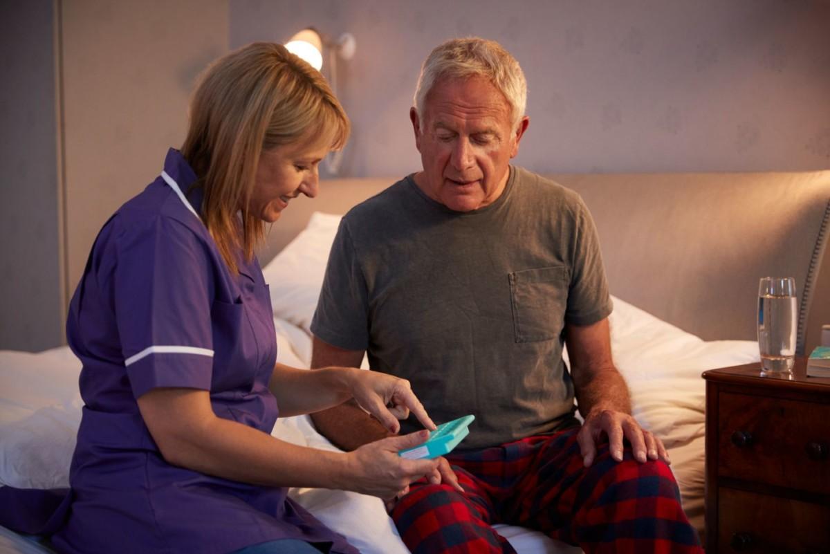 nurse helping senior man to organize medication PMRMCK