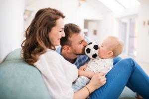 young family with a baby boy at home sitting on VFZLY