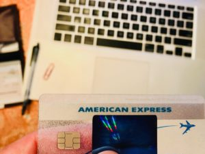 american express card with laptop checkbook and office supplies in the background on a table travel t YVPnNO