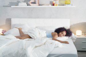 black woman sleeping alone in large bed NFHJE