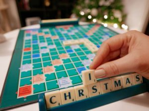 playing scrabble hand holding a scrabble letter letter tiles winter holidays christmas time christmas t kRJWZK
