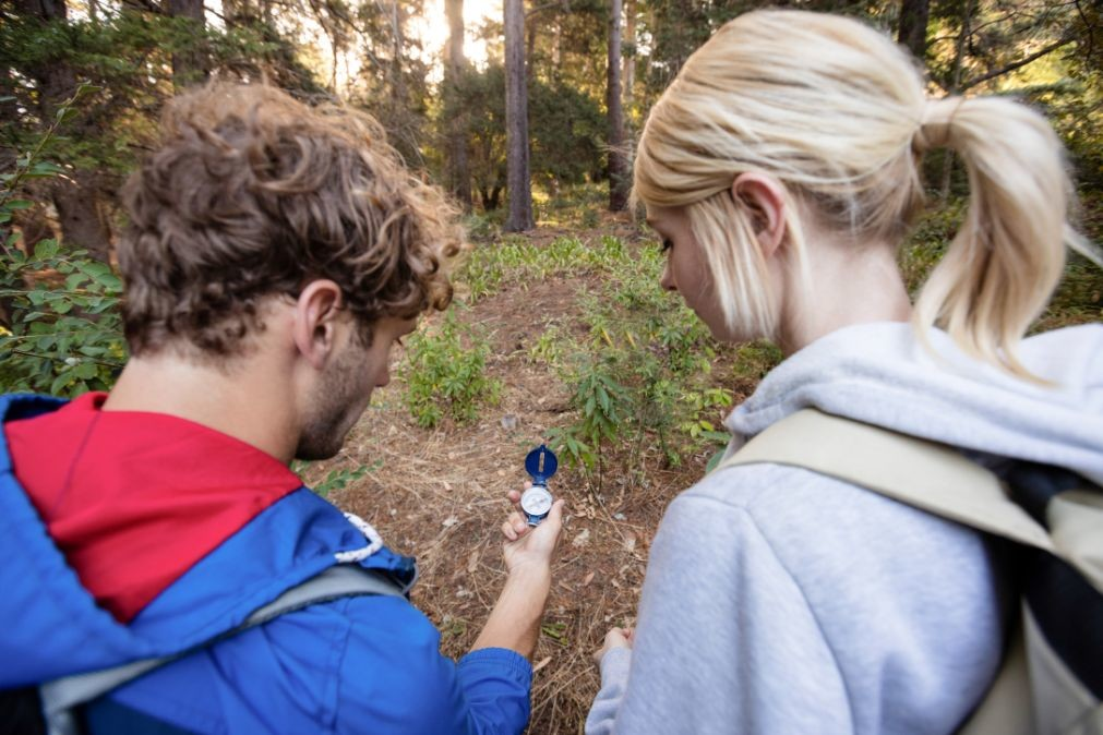 rear-view-of-hiking-couple-checking-the-compass-7PAVKYE