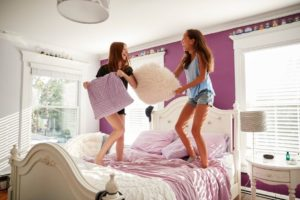 two teenage girls standing on a bed having a PEYWHBK