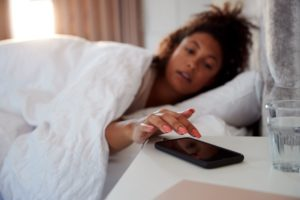 woman waking up in bed reaches out to turn off RSEMVY