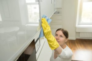 young attractive woman cleaning an upper surface PBDBDVM
