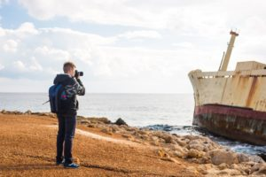 young photographer on the beach traveler PDS