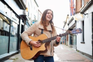 female musician busking playing acoustic guitar CWWHRB